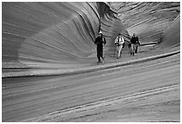 Hikers walk out of the Wave. Vermilion Cliffs National Monument, Arizona, USA ( black and white)