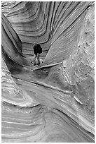 Hiker with backpack on a side formation of the Wave. Coyote Buttes, Vermilion cliffs National Monument, Arizona, USA (black and white)