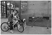 Girls on bikes and puppy parking. Telluride, Colorado, USA ( black and white)