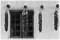 Yellow wall with ristras and blue window. Taos, New Mexico, USA (black and white)