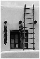 Strings of red peppers and ladder on building in pueblo style. Taos, New Mexico, USA (black and white)