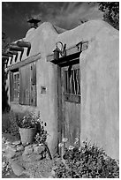 Flowers, adobe wall, and weathered door. Santa Fe, New Mexico, USA (black and white)