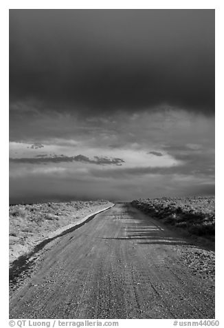 Dirt road under storm clouds. New Mexico, USA (black and white)