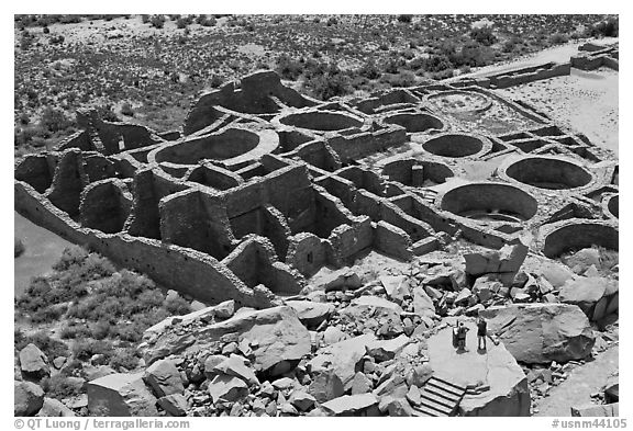 Tourists inspecting the complex room arrangement of Pueblo Bonito. Chaco Culture National Historic Park, New Mexico, USA (black and white)