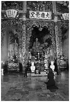 Woman praying at the altar. Ho Chi Minh City, Vietnam (black and white)