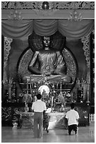 Men worshipping in front of a large Buddha state, Xa Loi pagoda, district 3. Ho Chi Minh City, Vietnam (black and white)