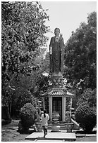 Woman praying under a large buddhist statue. Ho Chi Minh City, Vietnam (black and white)