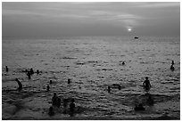 People bathing in Gulf of Thailand waters at sunset. Phu Quoc Island, Vietnam (black and white)