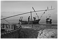 Fishermen pulling net onto skiff. Phu Quoc Island, Vietnam (black and white)