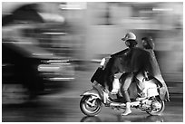 Women riding scooter in the rain. Ho Chi Minh City, Vietnam (black and white)