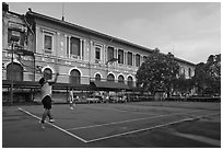 Men play tennis in front of colonial-area courthouse. Ho Chi Minh City, Vietnam ( black and white)
