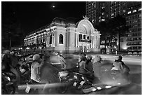 Motorbikes and colonial-area Opera House at night. Ho Chi Minh City, Vietnam ( black and white)