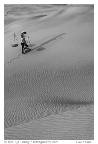 Woman with yoke baskets on sands. Mui Ne, Vietnam