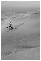 Rippled red sand dunes and woman with baskets. Mui Ne, Vietnam (black and white)