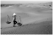 Woman carrying two baskets on shoulder pole. Mui Ne, Vietnam (black and white)