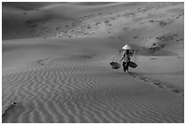 Woman with conical hat carries pannier baskets. Mui Ne, Vietnam (black and white)