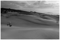 Coastal sand dunes with sea in distance and local woman. Mui Ne, Vietnam (black and white)