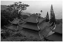 Temple rooftop overlooking plains in mist. Ta Cu Mountain, Vietnam (black and white)