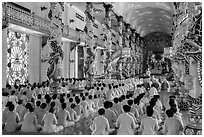 Rows of worshippers in Great Temple of Cao Dai. Tay Ninh, Vietnam (black and white)