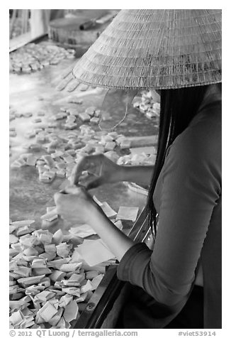Woman wearing conical hat wrapping coconut candy, Phoenix Island. My Tho, Vietnam
