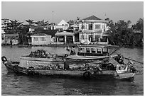 People moving pinapples from boat to boat on river. Can Tho, Vietnam (black and white)