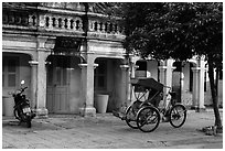 Motorcyle and cyclo in front of old townhouses. Hoi An, Vietnam ( black and white)