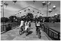 Girls on bicycle cross bridge festoned with lanterns. Hoi An, Vietnam (black and white)