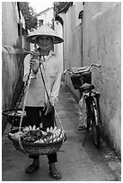 Fruit vendor carrying bananas. Hoi An, Vietnam (black and white)