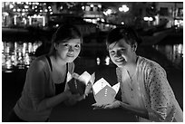 Two women lighted by candle box at night. Hoi An, Vietnam (black and white)