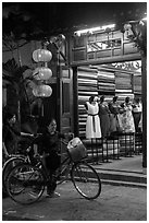 Women with bicycles in front of taylor shop. Hoi An, Vietnam (black and white)