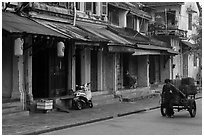 Man pulling cart in front of old townhouses. Hoi An, Vietnam ( black and white)
