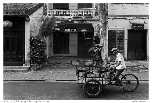 Man riding tricycle cart in front of old townhouses. Hoi An, Vietnam