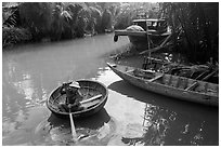 Man rows coracle boat in river channel. Hoi An, Vietnam (black and white)
