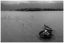 Man rowing coracle boat in lagoon. Vietnam (black and white)