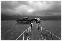 Pier leading to restaurant on stilts. Vietnam (black and white)