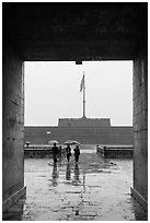 Tourists with unbrellas and flag monument, citadel. Hue, Vietnam (black and white)