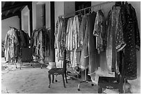 Coat hangers with silk robes in imperial style, citadel. Hue, Vietnam (black and white)