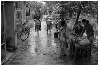 Canalside street with bicyclists and food stand, Thanh Toan. Hue, Vietnam (black and white)