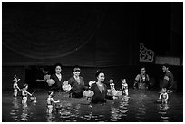 Puppeters coming from behind the bamboo screen after performance, Thang Long Theatre. Hanoi, Vietnam (black and white)