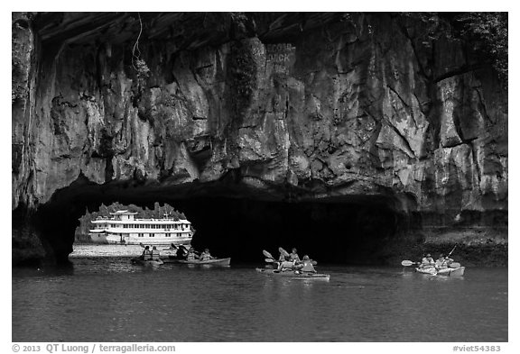 Kayaks floating through Luon Can tunnel. Halong Bay, Vietnam