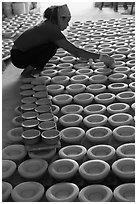 Woman laying ceramic bowls to dry in workshop. Bat Trang, Vietnam ( black and white)