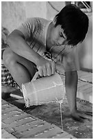 Man pouring clay into molds in ceramic workshop. Bat Trang, Vietnam ( black and white)