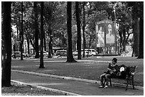 Relaxing on a public bench in park. Ho Chi Minh City, Vietnam (black and white)