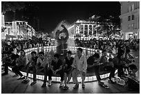 People sitting on fountain at night, New Year eve. Ho Chi Minh City, Vietnam ( black and white)