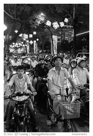 Street packed with motorbikes and bicycle riders at night. Ho Chi Minh City, Vietnam
