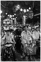 Street packed with motorbikes and bicycle riders at night. Ho Chi Minh City, Vietnam ( black and white)
