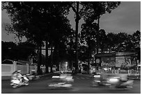 Blurred motorbikes at dusk and tall trees next to Van Hoa Park. Ho Chi Minh City, Vietnam (black and white)
