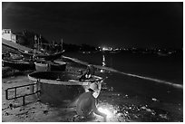Man with fire next to coracle boat at night. Mui Ne, Vietnam (black and white)