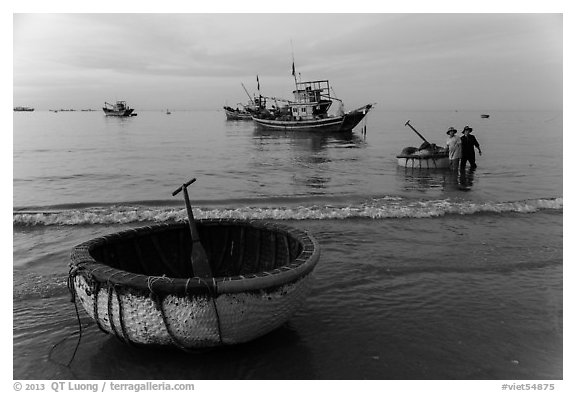 Coracle and fishing boats at dawn. Mui Ne, Vietnam (black and white)