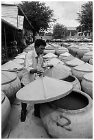 Man lifting covers of jars with fermented fish sauce. Mui Ne, Vietnam (black and white)
